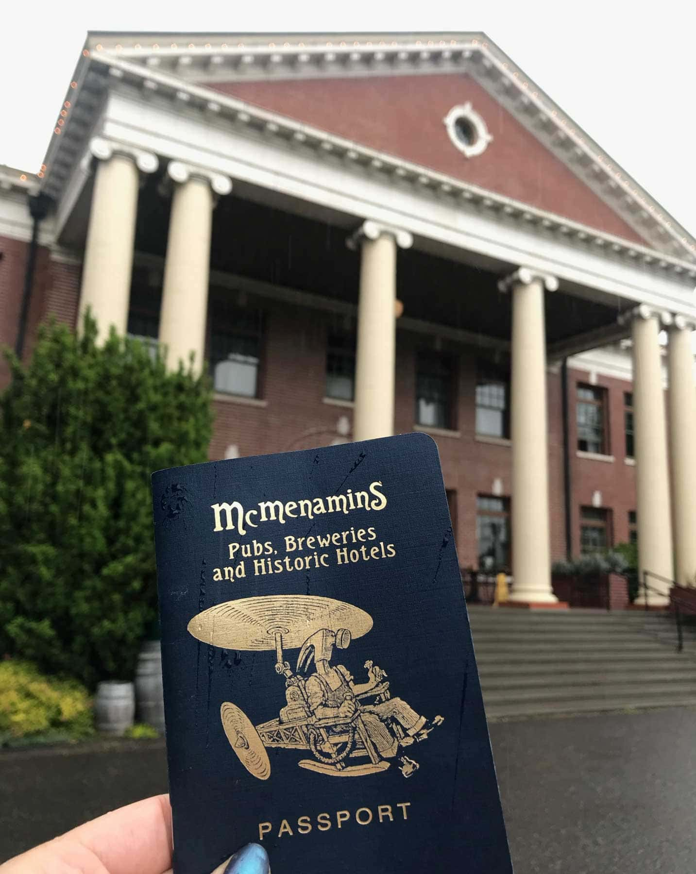 A hand holds the McMenamins Passport in front of the Grand Lodge's white columns outside.