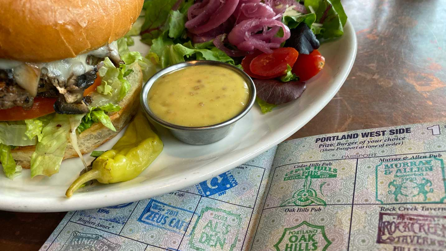 A burger with a side salad sits on a completed passport page.