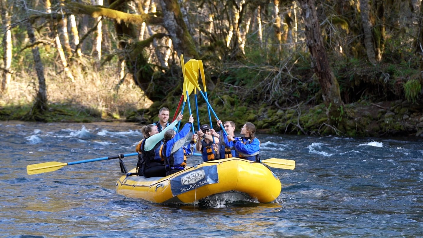 A group rafting give high-fives with their paddles