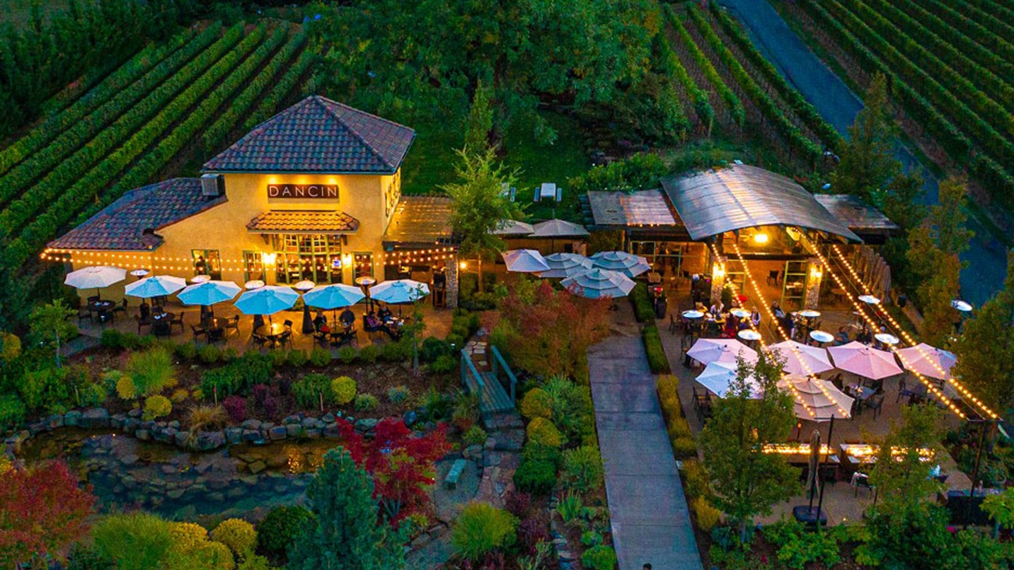A building, surrounded by vineyards, is lit up in the evening
