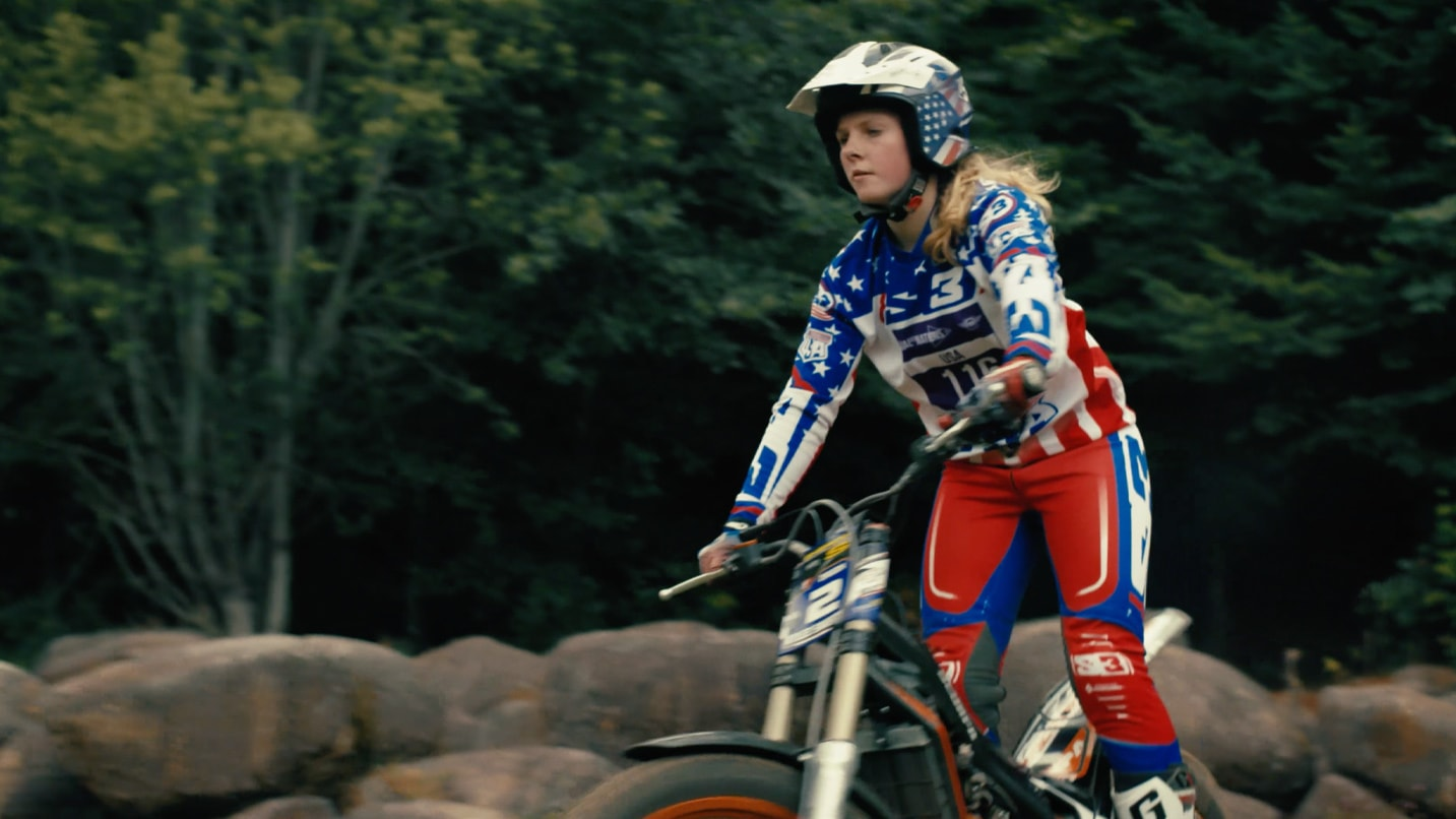 A woman in protective riding gear and helmet rides a dirtbike