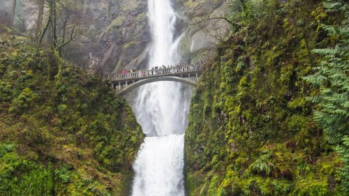 A bridge goes between a double tiered waterfall