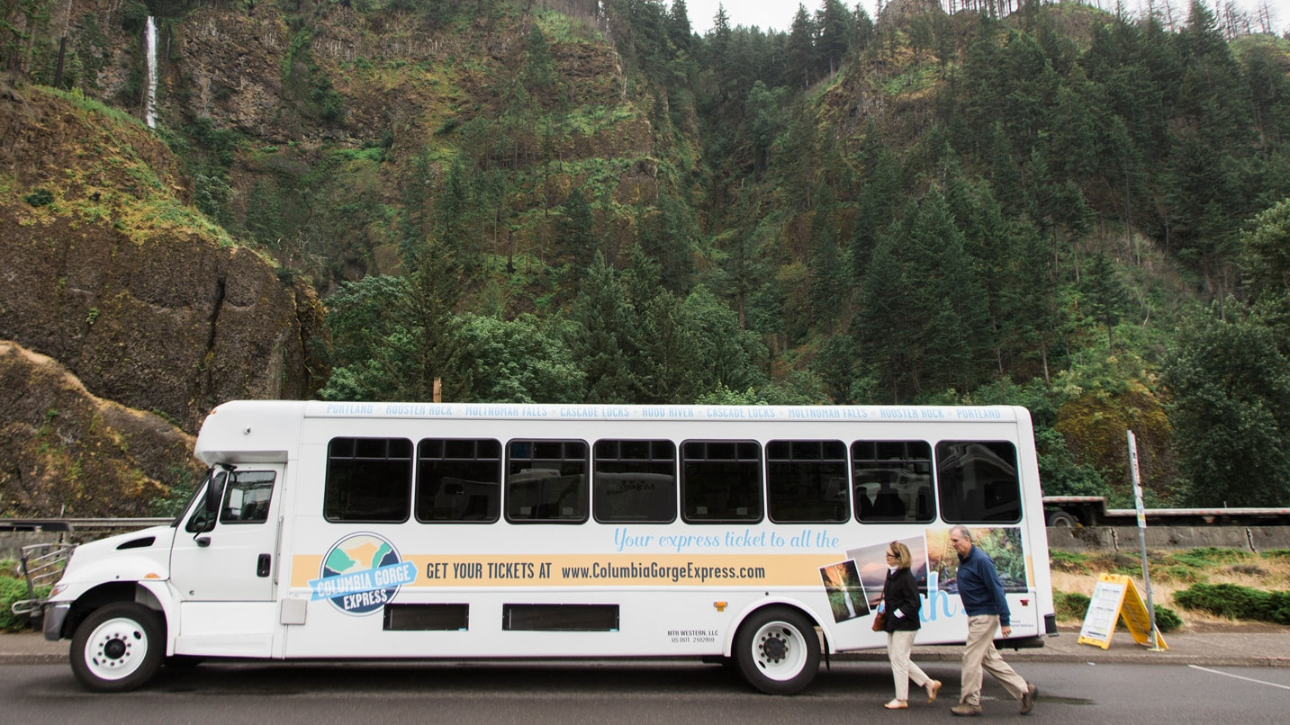 A shuttle bus is parked in front of a waterfall