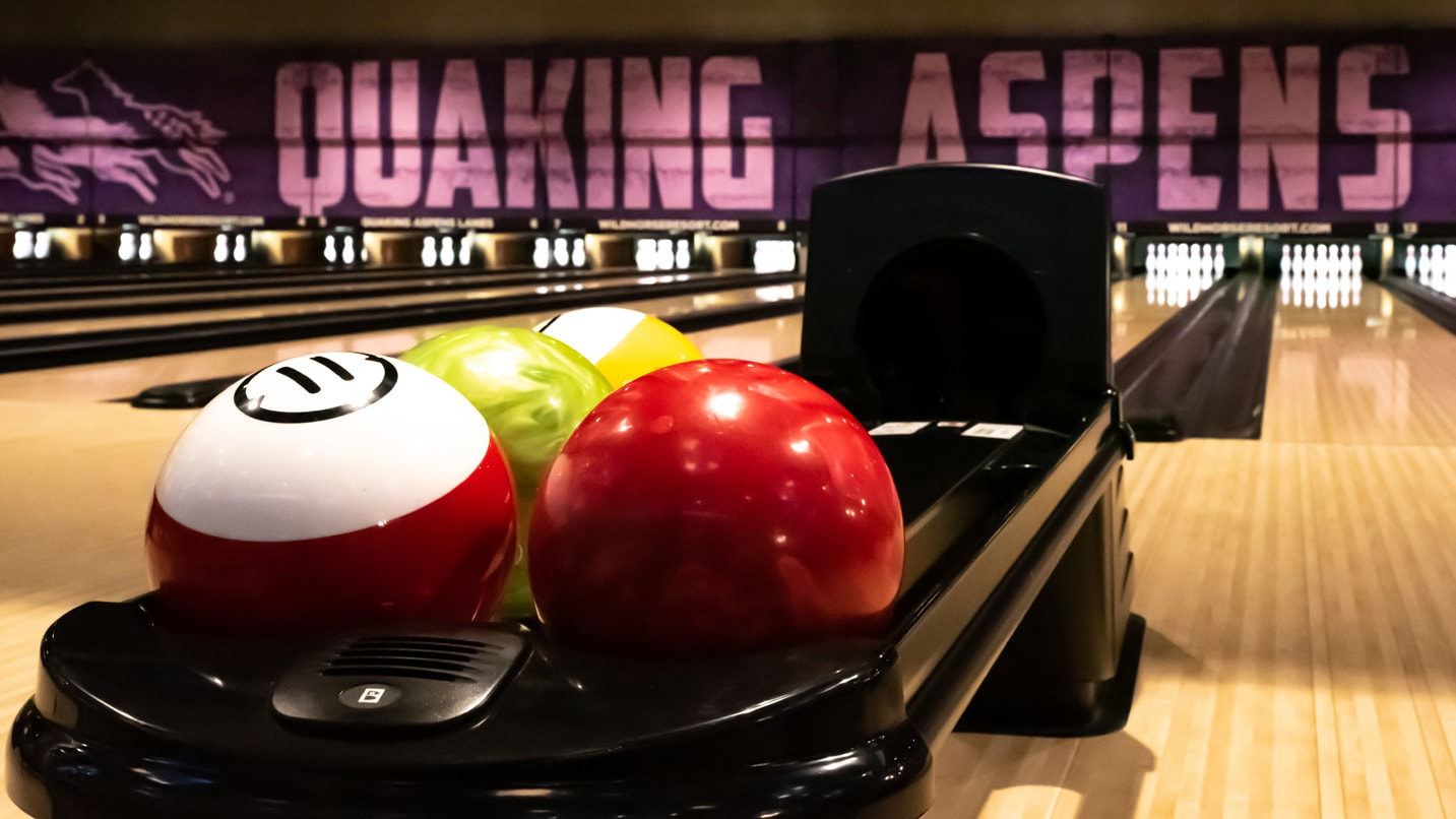Bowling balls are set up in a bowling lane