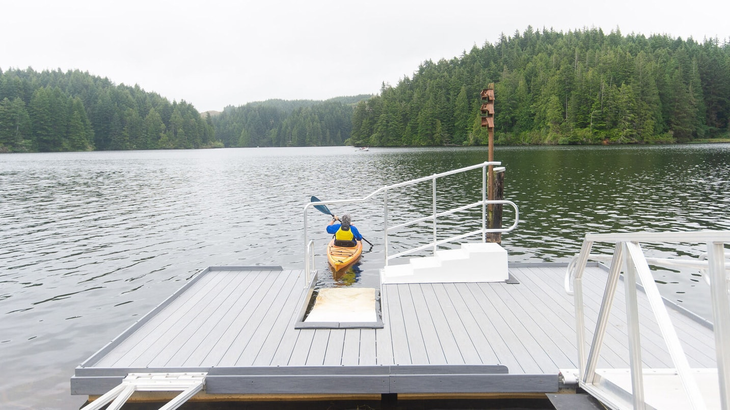 A kayak launches from a boat ramp with a slide in feature