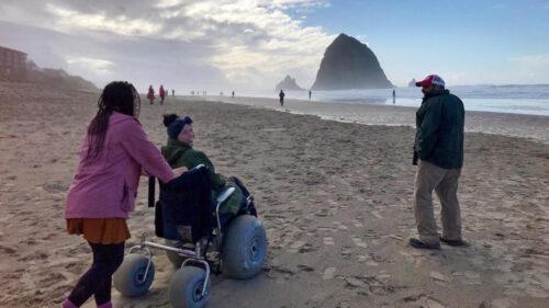 A woman explores the beach in a wheelchair