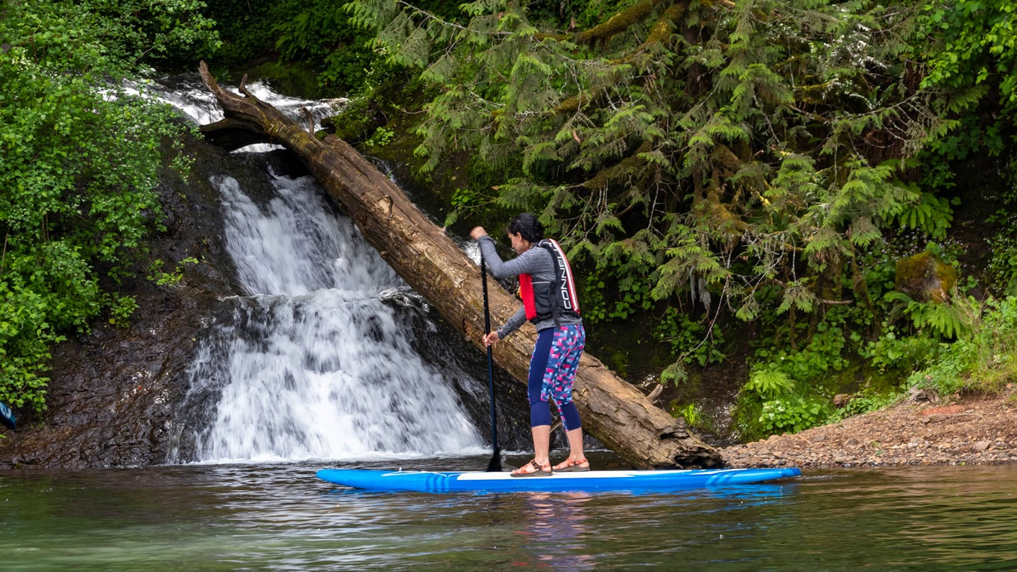 A man paddle boards past a small waterfall