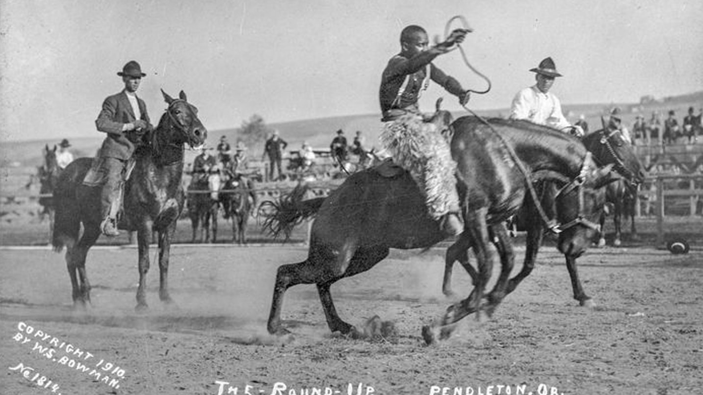 A historic photo shows a Black man riding a horse at a rodeo