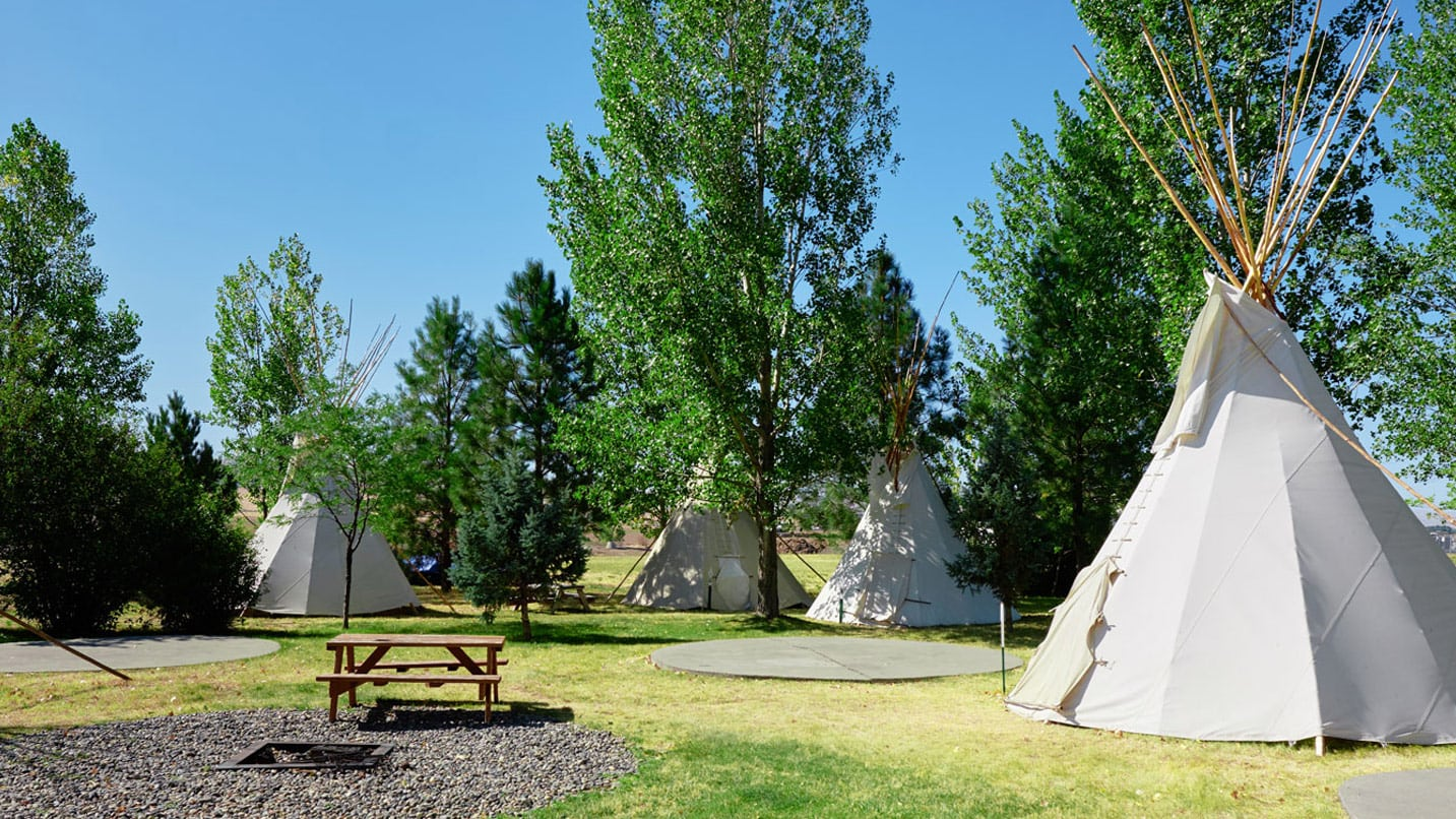 White canvas tipis are set up around a picnic table
