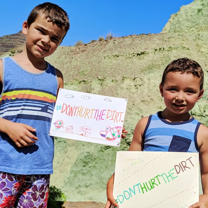 Two children holding signs that say don't hurt the dirt