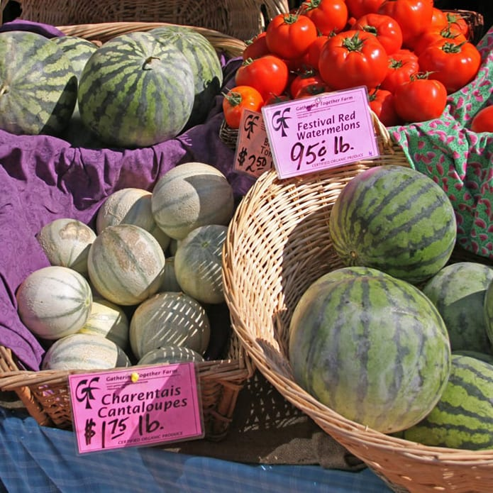 Watermelon, cantelope and tomatoes on display at farmers market booth