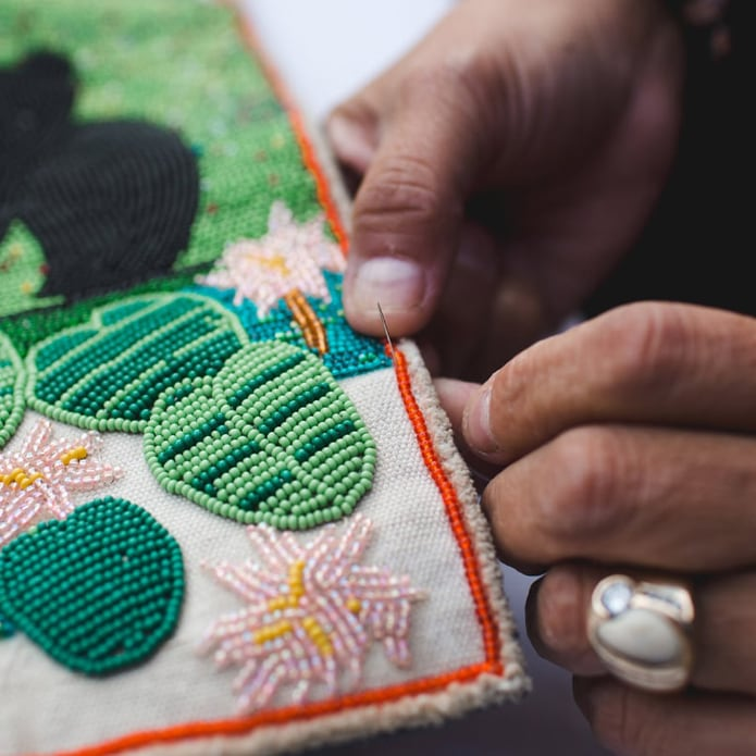 Hands of an Indigenous person making bead art.