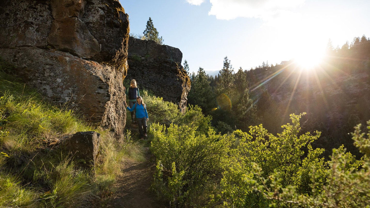 Two people walk along a trail alongside cliffs at sunset