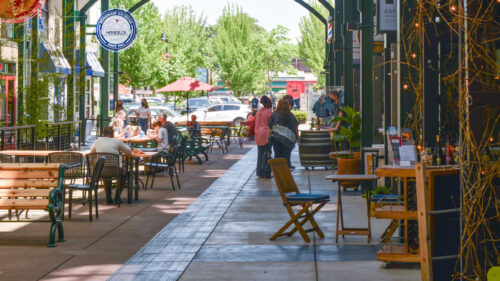 People are in the distance and sidewalk tables are in the foreground on a downtown street.