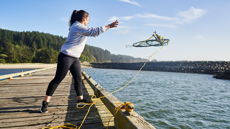 A woman throwing a crab pot off a dock