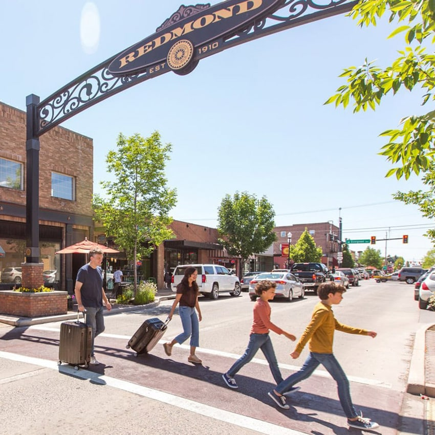 Family of four crossing mainstreet of Redmond with luggage