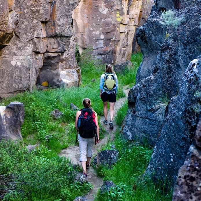 Two people walk on a path between rock columns