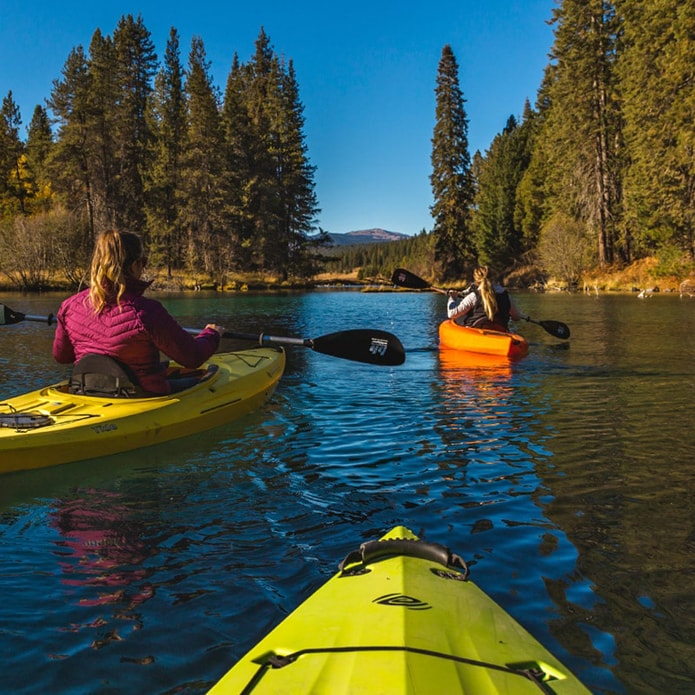 Three brightly colored kayaks skimming the water