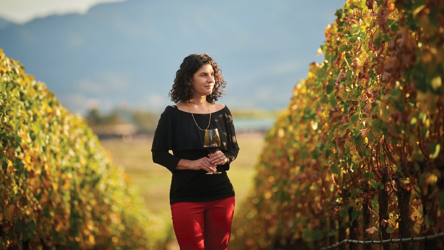 A woman standing in a row of fall vineyards