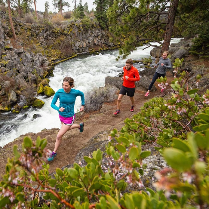 three people trail running alongside a creek.