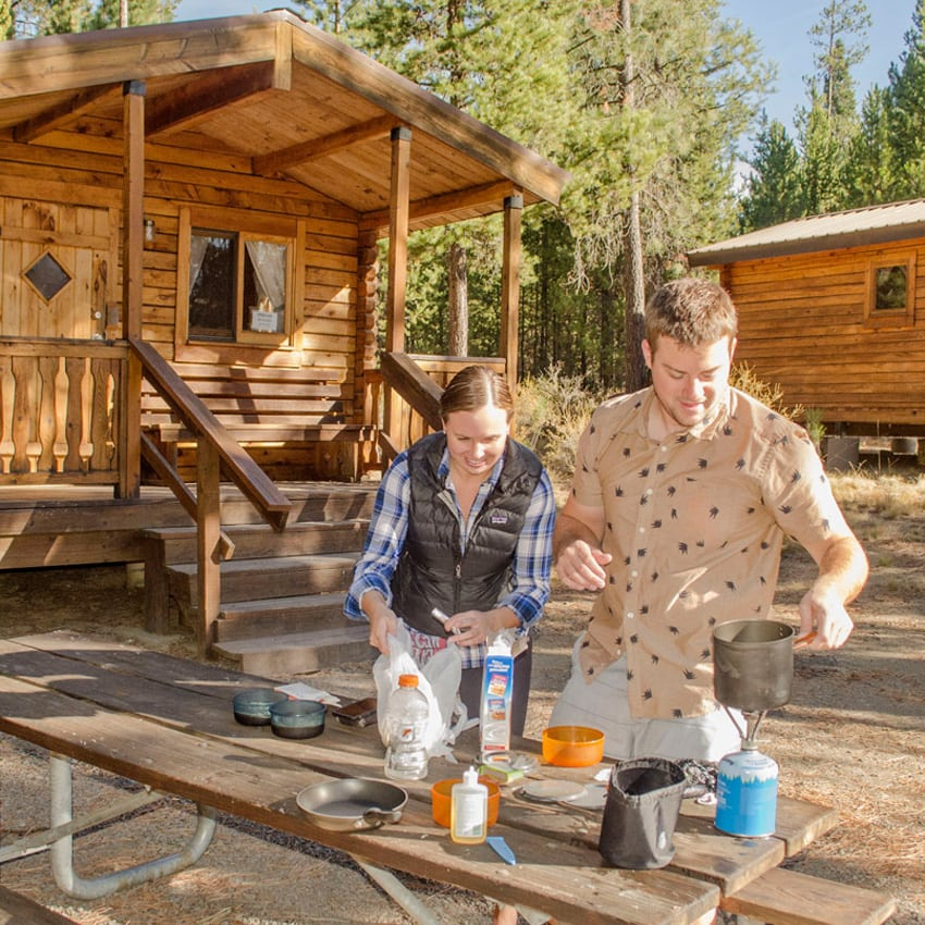 couple prepping dinner at picnic table with cabin in background.