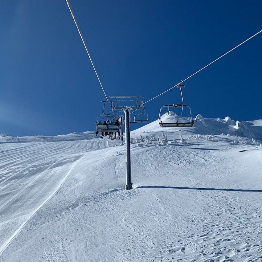 people riding a chairlift to the summit of Mt. Bachelor