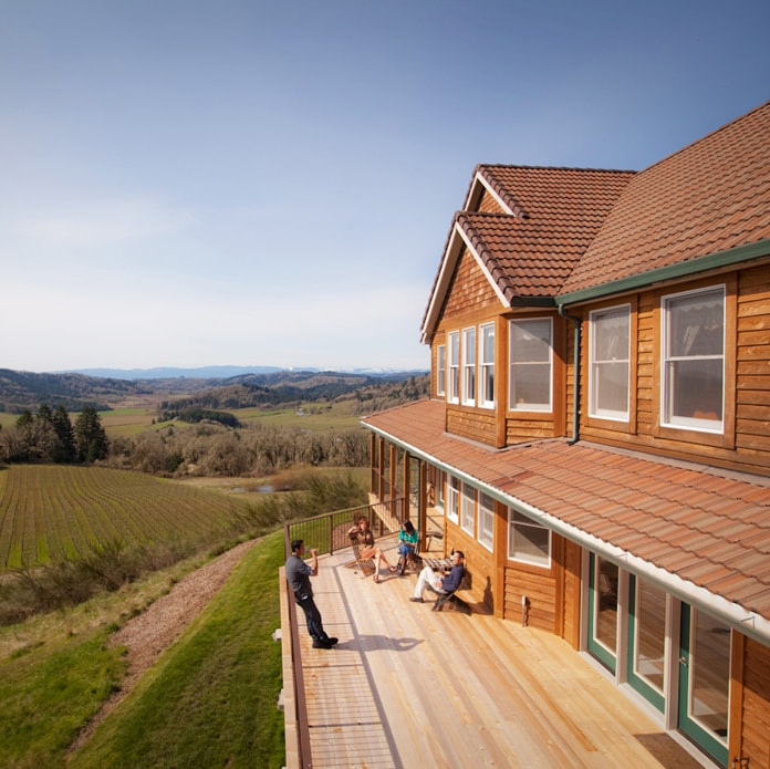 People enjoying wine and view of vineyard from deck of Youngberg Hill