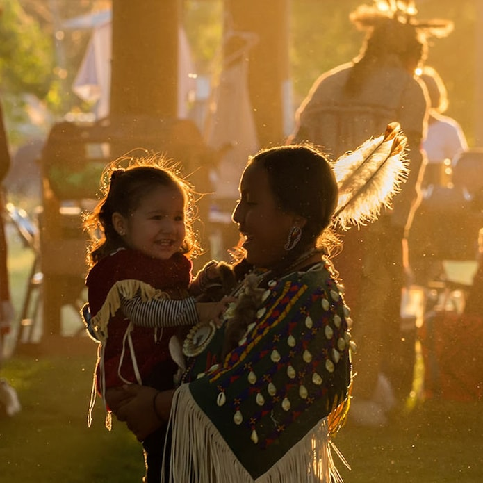 Indigenous woman holding a young child at a powwow with attendees in regalia in background.