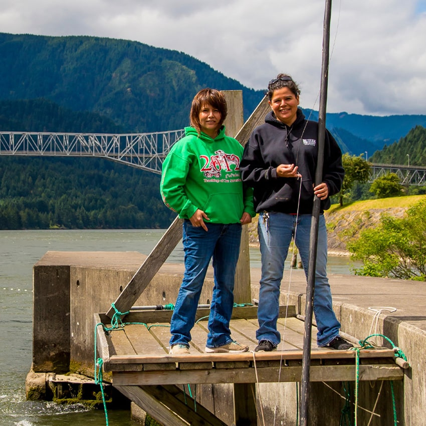 Two indigenous women fishing on Columbia River with Bridge of Gods in background.