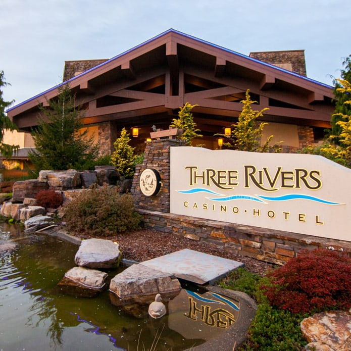 View of Three Rivers Resort buildign with pond and duck in foreground.
