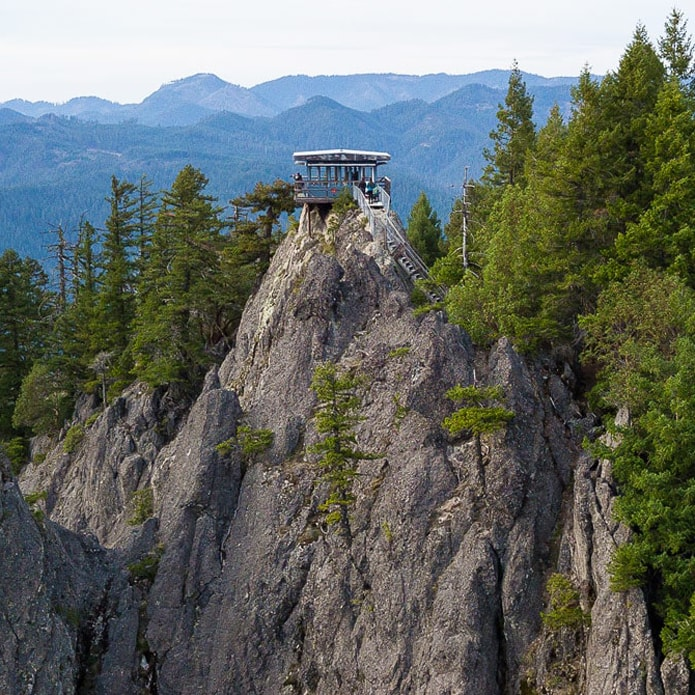 Fire lookout tower perched atop Acker Rock with mountains in the distance.